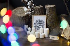 Composição de um quadro com um ano novo feliz da inscrição, velas, fellings das árvores contra um fundo escuro, e o blinkin foto de stock