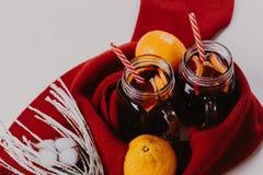 Composição decorada das canecas com vinho ferventado com especiarias no lenço feito malha, fim acima imagens de stock royalty free