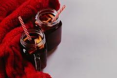 Composição decorada das canecas com vinho ferventado com especiarias no lenço feito malha, fim acima fotos de stock