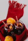 Composição decorada das canecas com vinho ferventado com especiarias no lenço feito malha, fim acima foto de stock