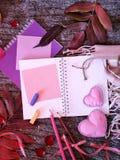 Composição decorativa sazonal das folhas, corações do feltro, caderno vazio, cumprimentando o papel, lápis, pétalas cor-de-rosa e imagem de stock