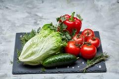 Composição deliciosa de legumes frescos sortidos e de ervas no fundo textured branco, vista superior, foco seletivo Fotos de Stock Royalty Free