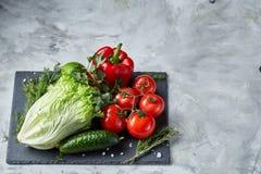Composição deliciosa de legumes frescos sortidos e de ervas no fundo textured branco, vista superior, foco seletivo Imagem de Stock