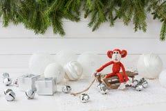 Composição do ano novo com o macaco vermelho no trenó Imagens de Stock