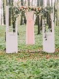 A composição do arco sob a forma das portas brancas decoradas com as flores brancas e vermelhas e o vestido cor-de-rosa longo é Imagens de Stock Royalty Free