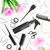 A composição do cabeleireiro com pulverizador, tesouras, pentes, prendedor de cabelo e tulipas floresce no fundo branco Conceito  Imagem de Stock