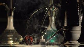 Composição do cachimbo de água na tabela O cachimbo de água está mudando cores quando a nuvem enorme do fumo grosso for envolver filme