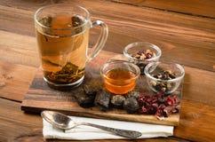 Composição do chá com a colher velha na madeira Foto de Stock