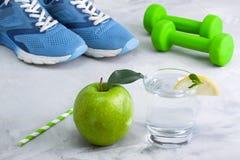 Composição do esporte com a maçã de vidro da água do material desportivo Imagens de Stock Royalty Free