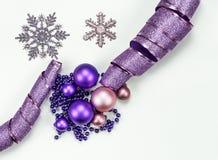 Composição do Feliz Natal e do ano novo feliz: Brinquedos do Natal, fita roxa, chaplet azul, flocos de neve fotografia de stock royalty free