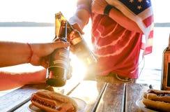 Composição do feriado com as garrafas múltiplas da cerveja e dos cachorros quentes, bandeira americana Grupo de pessoas que comem Imagens de Stock