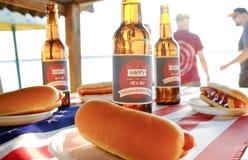 Composição do feriado com as garrafas múltiplas da cerveja e dos cachorros quentes, bandeira americana Grupo de pessoas que comem Foto de Stock