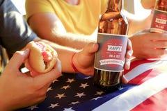 Composição do feriado com as garrafas múltiplas da cerveja e dos cachorros quentes, bandeira americana Grupo de pessoas que comem Fotografia de Stock