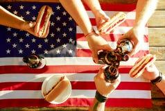 Composição do feriado com as garrafas múltiplas da cerveja e dos cachorros quentes, bandeira americana Grupo de pessoas que comem Foto de Stock Royalty Free