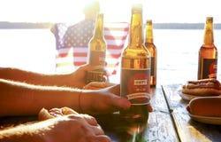 Composição do feriado com as garrafas múltiplas da cerveja e dos cachorros quentes, bandeira americana Grupo de pessoas que comem Fotos de Stock Royalty Free