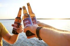 A composição do feriado, fim acima dos homens entrega guardar garrafas da cerveja Grupo de pessoas que comemora o Dia da Independ Fotografia de Stock Royalty Free