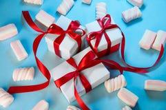 Composição do feriado do Natal O branco do presente do ano novo encaixota a fita vermelha com os marshmallows no fundo azul Confi imagens de stock royalty free