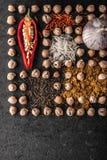 Composição do grão-de-bico, dos vegetais e da especiaria no vertical de pedra escuro Foto de Stock