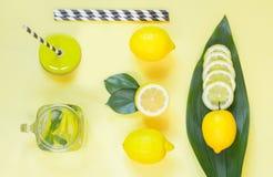 Composição do limão do verão para cozinhar a limonada da desintoxicação com hortelã e gelo no frasco de pedreiro no amarelo Conce Imagens de Stock Royalty Free