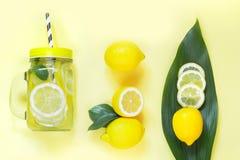 Composição do limão do verão para cozinhar a limonada da desintoxicação com hortelã e gelo no frasco de pedreiro no amarelo Conce Fotografia de Stock Royalty Free