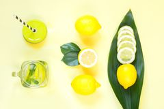 Composição do limão do verão para cozinhar a limonada da desintoxicação com hortelã e gelo no frasco de pedreiro no amarelo Conce Imagens de Stock
