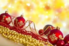 Composição do Natal As quinquilharias vermelhas, fitas no feriado iluminam o fundo Fotos de Stock