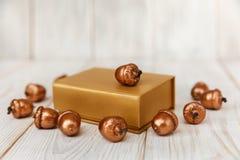 Composição do Natal Caixa atual dourada e bolotas douradas Tabela de madeira branca fotos de stock