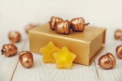Composição do Natal Caixa atual dourada e bolotas douradas Tabela de madeira branca, estrelas do jujuba Imagem de Stock