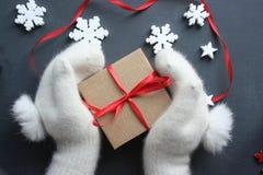 Composição do Natal Caixa de presente com a fita vermelha do cetim que guarda as mãos nos mitenes brancos da pele foto de stock royalty free