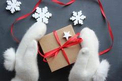 Composição do Natal Caixa de presente com a fita vermelha do cetim que guarda as mãos nos mitenes brancos da pele fotos de stock