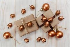 Composição do Natal Caixas atuais com guita e papel do ofício, bolotas douradas e bolas Tabela de madeira branca Imagens de Stock
