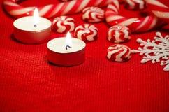 Composição do Natal com os doces e velas vermelhos e brancos Foto de Stock Royalty Free
