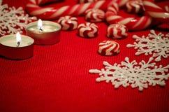 Composição do Natal com os doces e velas vermelhos e brancos Fotografia de Stock Royalty Free