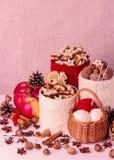 Composição do Natal com os frascos feitos malha para a cookie, maçãs, spic Imagem de Stock