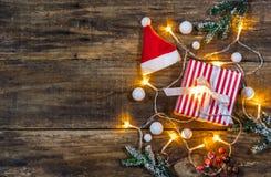 Composição do Natal com presente, tampão de Santa e luzes Fotos de Stock Royalty Free
