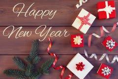 Composição do Natal de caixas de presente vermelhas e brancas, de fitas decorativas e de ramos de uma árvore de Natal inscription fotografia de stock royalty free