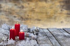 Composição do Natal e do ano novo Velas do Lit, caixas de presente, festões, na placa de madeira nevado sobre a parede do ald imagens de stock royalty free