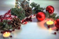 Composição do Natal em bolas vermelhas do fundo de madeira, em presentes, e no ramo de árvore verde com cones, vela ardente do Na Imagem de Stock Royalty Free