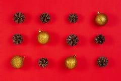 Composição do Natal Teste padrão feito da decoração dos cones do pinho, a amarela e a vermelha do Natal no fundo vermelho foto de stock