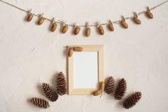 Composição do outono com quadro de madeira Bolota com os pregadores de roupa na linha de roupa corda Pegs de madeira Configuração imagens de stock
