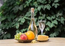 A composição do queijo, as uvas, os pêssegos, o branco, as garrafas e os vidros wine em uma mesa redonda de madeira No pátio Foto de Stock Royalty Free