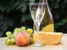 A composição do queijo, as uvas, os pêssegos, o branco, as garrafas e os vidros wine em uma mesa redonda de madeira No pátio Fotografia de Stock Royalty Free