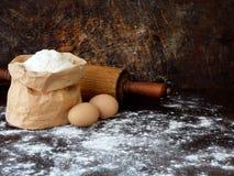 Composição do saco da farinha de trigo, ovos e pino do rolo Preparação para a massa de amasso, cozendo no fundo escuro Espaço par Imagem de Stock
