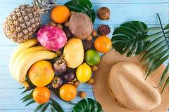 Composição do verão Folhas de palmeira tropicais, chapéu, muitos frutos no fundo de madeira azul Conceito do verão Configuração l fotos de stock
