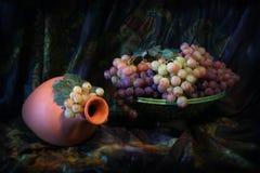Composição do vesel cerâmico tradicional da água do Uzbeque, do prato cerâmico e das uvas Fotografia de Stock