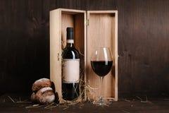 Composição do vinho tinto com a garrafa do pão na caixa e no copo de vinho no fundo de madeira marrom Fotografia de Stock
