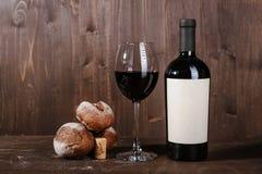 Composição do vinho tinto com pão, duas garrafas na caixa e copo de vinho no fundo de madeira Fotos de Stock Royalty Free