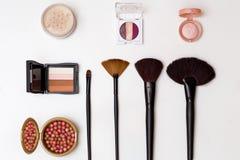 A composição dos cosméticos escova o pó da fundação da sombra para os olhos na opinião superior do fundo branco Fotos de Stock Royalty Free