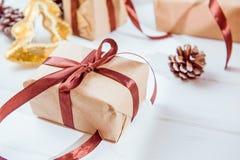 Composição dos feriados do Natal com os presentes no papel do ofício com a fita do cetim no fundo de madeira branco com espaço da Imagem de Stock