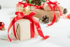 Composição dos feriados do Natal com os presentes no papel do ofício com a fita vermelha do cetim no fundo de madeira branco com  Fotos de Stock Royalty Free